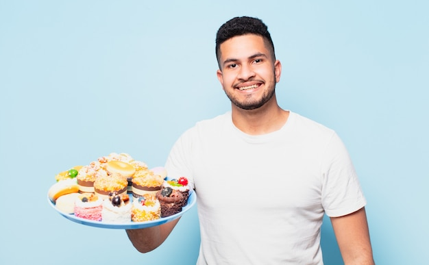 Jonge spaanse man gelukkige uitdrukking met cupcakes