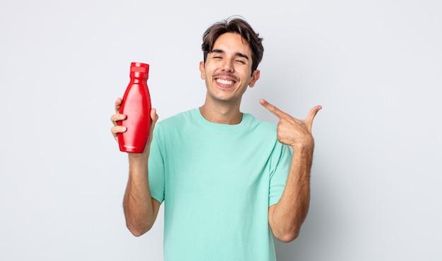 Jonge spaanse man glimlachend vol vertrouwen wijzend naar eigen brede glimlach. ketchup-concept