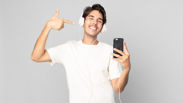 Jonge spaanse man glimlachend vol vertrouwen wijzend naar eigen brede glimlach met koptelefoon en smartphone