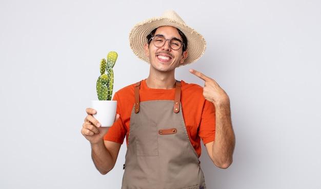 Jonge spaanse man glimlachend vol vertrouwen wijzend naar eigen brede glimlach. tuinman met cactusconcept