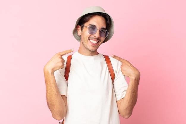 Jonge spaanse man glimlachend vol vertrouwen wijzend naar eigen brede glimlach. zomer concept