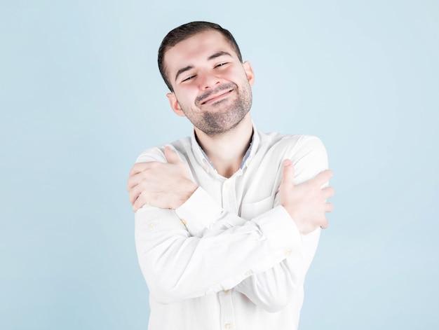 Jonge spaanse man in vrijetijdskleding omhelst zichzelf gelukkig en positief, glimlachend vol vertrouwen. eigenliefde en zelfzorg