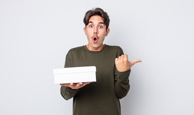 Jonge spaanse man kijkt verbaasd in ongeloof. witte doos concept