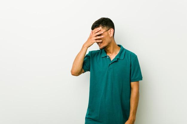 Jonge spaanse man knipperend naar de camera door vingers, beschaamd bedekkend gezicht.