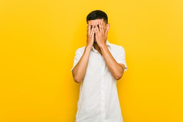 Jonge spaanse man knippert angstig en nerveus door vingers.