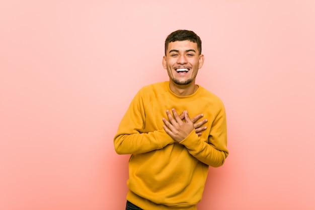 Jonge spaanse man lachen houden handen op het hart, van geluk.