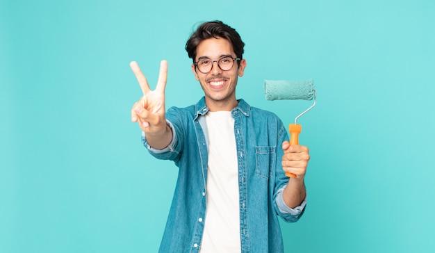 Jonge spaanse man lacht en ziet er gelukkig uit, gebaart overwinning of vrede en houdt een verfroller vast