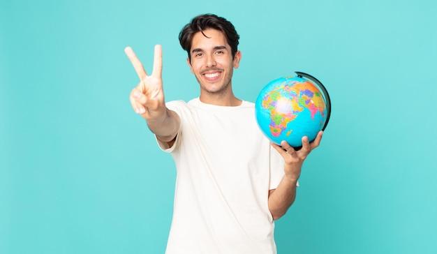 Jonge spaanse man lacht en ziet er gelukkig uit, gebaart overwinning of vrede en houdt een wereldbolkaart vast