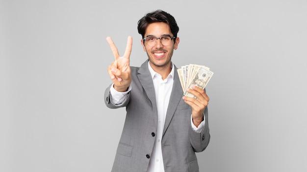 Jonge spaanse man lacht en ziet er gelukkig uit, gebarend naar overwinning of vrede