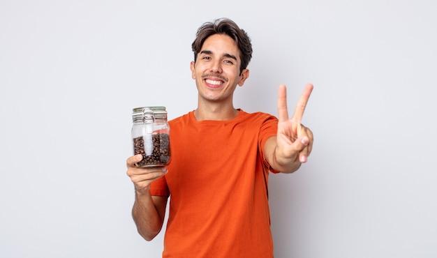 Jonge spaanse man lacht en ziet er gelukkig uit, gebarend overwinning of vrede. koffiebonen concept
