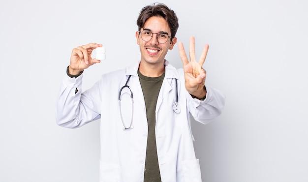 Jonge spaanse man lacht en ziet er vriendelijk uit, met nummer drie. arts met pillen fles concept