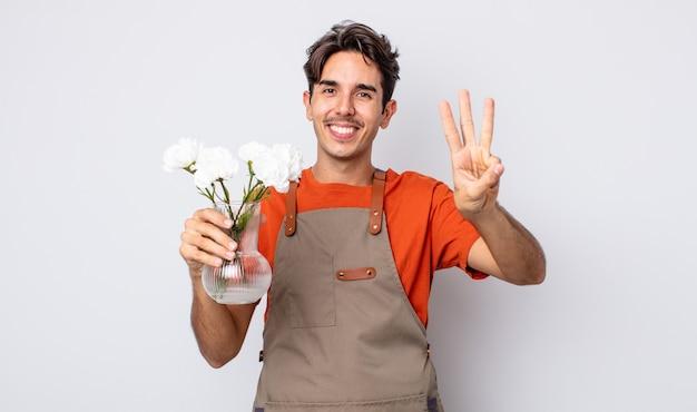 Jonge spaanse man lacht en ziet er vriendelijk uit, met nummer drie. bloemist concept