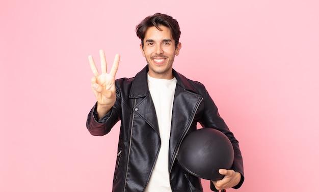 Jonge spaanse man lacht en ziet er vriendelijk uit, met nummer drie. motorrijder concept