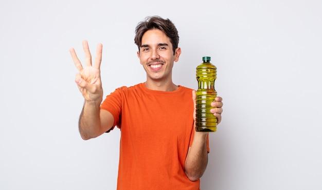 Jonge spaanse man lacht en ziet er vriendelijk uit, met nummer drie. olijfolie concept
