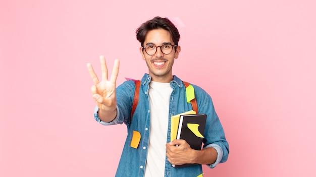 Jonge spaanse man lacht en ziet er vriendelijk uit, met nummer drie. studentenconcept