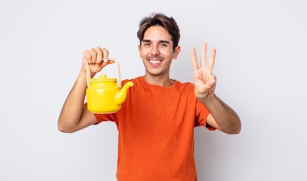 Jonge spaanse man lacht en ziet er vriendelijk uit, met nummer drie. theepot concept