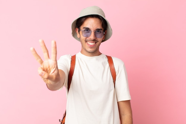 Jonge spaanse man lacht en ziet er vriendelijk uit, met nummer drie. zomer concept