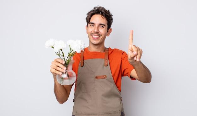 Jonge spaanse man lacht en ziet er vriendelijk uit, met nummer één. bloemist concept