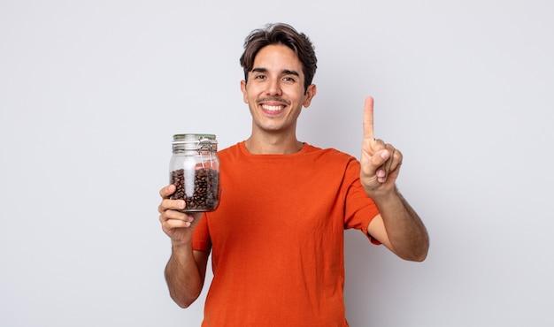 Jonge spaanse man lacht en ziet er vriendelijk uit, met nummer één. koffiebonen concept