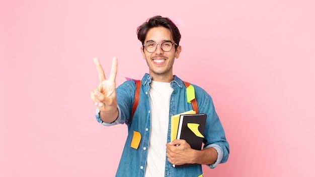 Jonge spaanse man lacht en ziet er vriendelijk uit, met nummer twee. studentenconcept