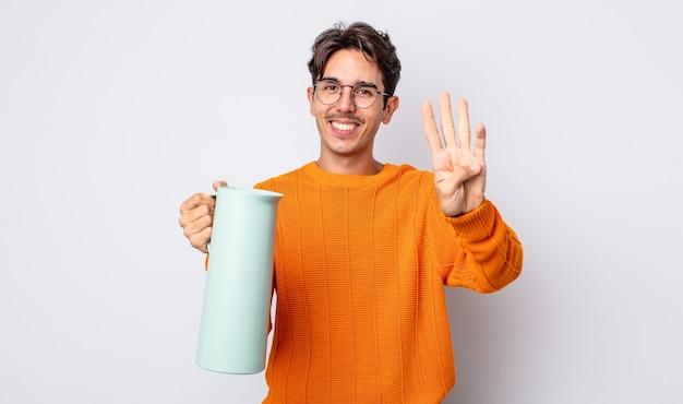 Jonge spaanse man lacht en ziet er vriendelijk uit, met nummer vier. thermos concept