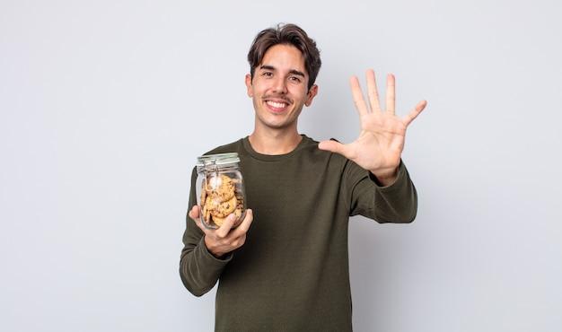 Jonge spaanse man lacht en ziet er vriendelijk uit, met nummer vijf. koekjes concept