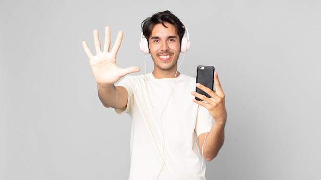 Jonge spaanse man lacht en ziet er vriendelijk uit, met nummer vijf met koptelefoon en smartphone