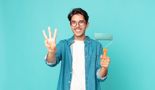 Jonge spaanse man lacht en ziet er vriendelijk uit, toont nummer drie en houdt een verfroller vast
