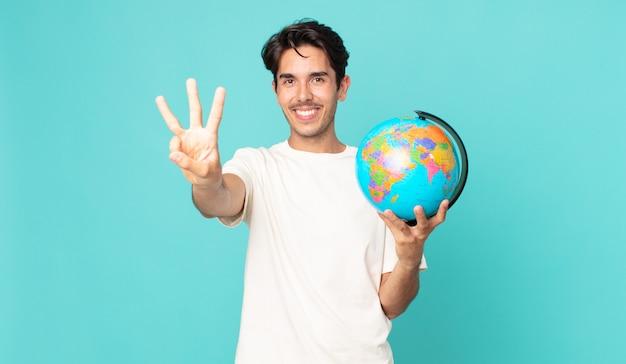 Jonge spaanse man lacht en ziet er vriendelijk uit, toont nummer drie en houdt een wereldbolkaart vast