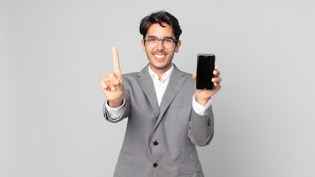 Jonge spaanse man lacht en ziet er vriendelijk uit, toont nummer één en houdt een smartphone vast