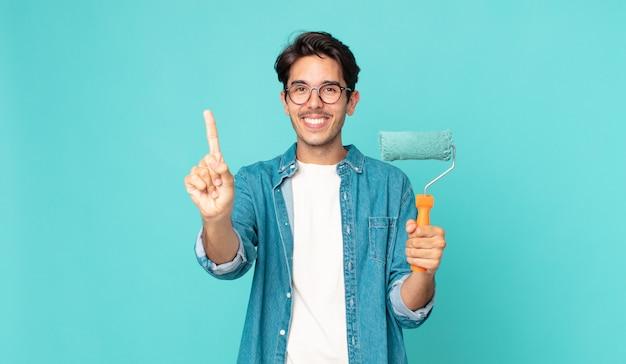 Jonge spaanse man lacht en ziet er vriendelijk uit, toont nummer één en houdt een verfroller vast