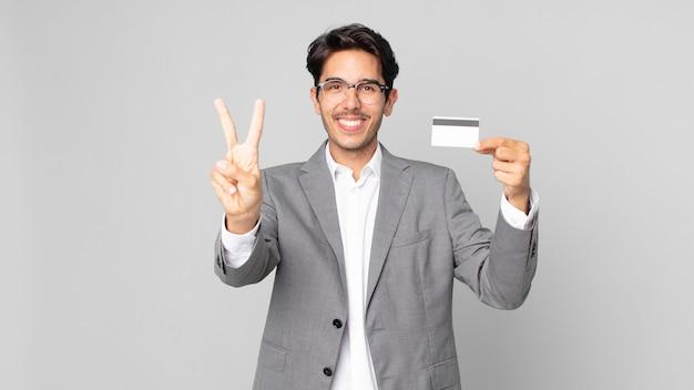 Jonge spaanse man lacht en ziet er vriendelijk uit, toont nummer twee en houdt een creditcard vast