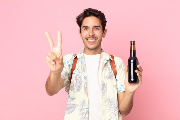 Jonge spaanse man lacht en ziet er vriendelijk uit, toont nummer twee en houdt een flesje bier vast