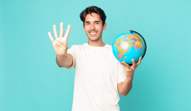 Jonge spaanse man lacht en ziet er vriendelijk uit, toont nummer vier en houdt een wereldbolkaart vast