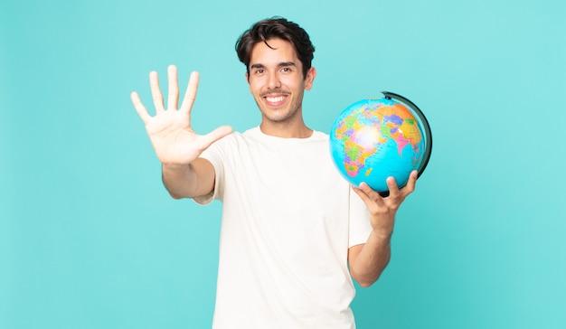 Jonge spaanse man lacht en ziet er vriendelijk uit, toont nummer vijf en houdt een wereldbolkaart vast