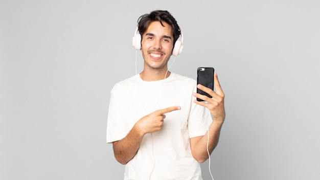 Jonge spaanse man lacht vrolijk, voelt zich gelukkig en wijst naar de zijkant met koptelefoon en smartphone