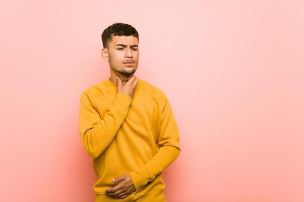 Jonge spaanse man lijdt pijn in de keel als gevolg van een virus of infectie.