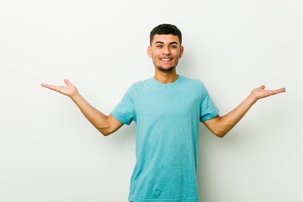 Jonge spaanse man maakt schaal met armen, voelt zich gelukkig en zelfverzekerd.