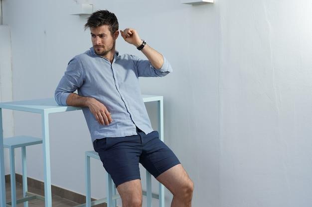 Jonge spaanse man met een blauw shirt poserend naast een bureau
