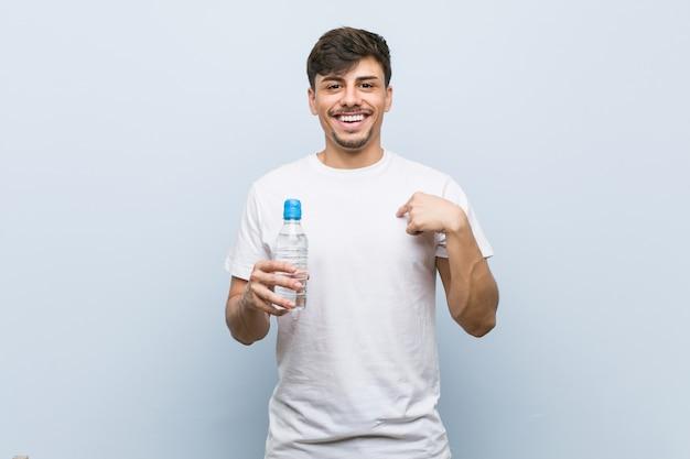 Jonge spaanse man met een fles water verrast wijzend op zichzelf, breed glimlachend.