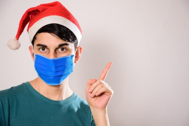 Jonge spaanse man met een gezichtsmasker en een kerstmuts die omhoog wijst
