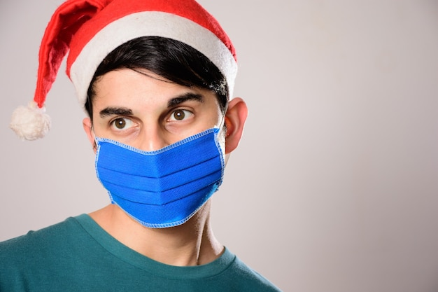 Jonge spaanse man met een gezichtsmasker en een kerstmuts opzij kijken