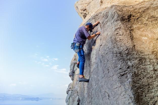 Jonge spaanse man met een touw die zich bezighoudt met de sporten van rotsklimmen op de rots