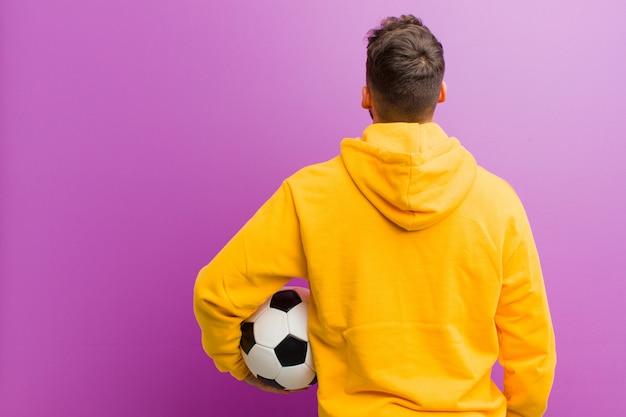 Jonge spaanse man met een voetbal tegen paars