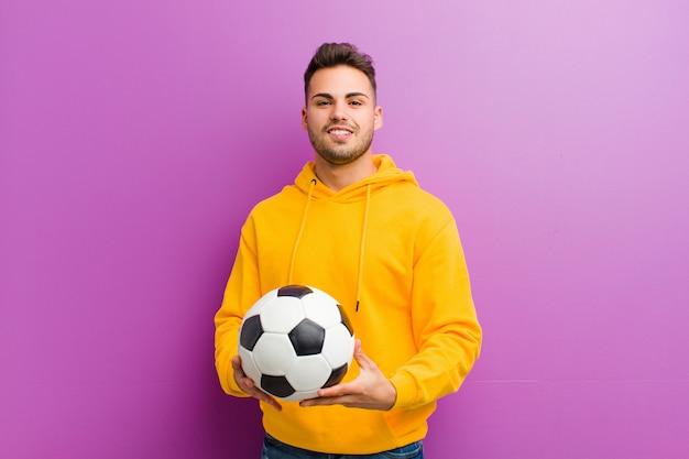 Jonge spaanse man met een voetbal tegen paarse achtergrond