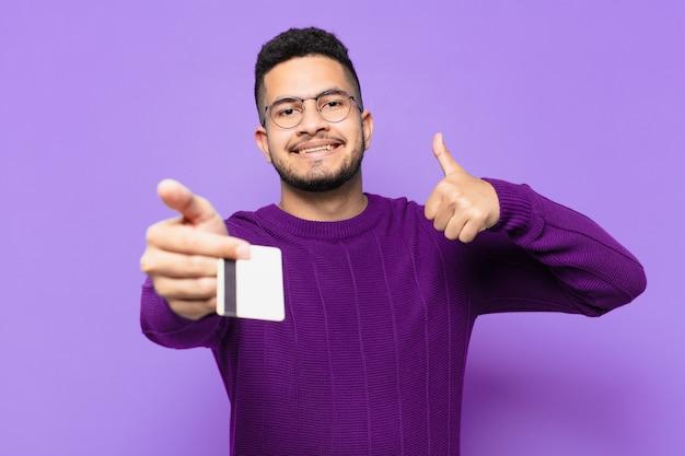 Jonge spaanse man met gelukkige uitdrukking en met een creditcard