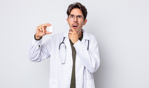 Jonge spaanse man met mond en ogen wijd open en hand op kin. arts met pillen fles concept