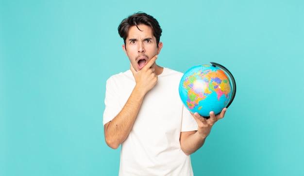 Jonge spaanse man met mond en ogen wijd open en hand op kin en met een wereldbolkaart