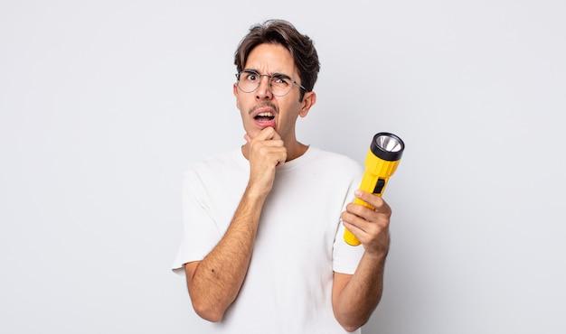 Jonge spaanse man met mond en ogen wijd open en hand op kin. lantaarn concept