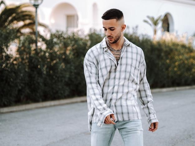 Jonge spaanse man met tatoeages die op straat poseert